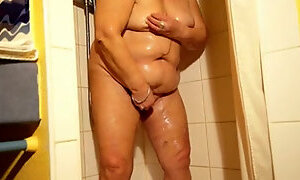 Granny in the shower rubs her wet twat and fingers it