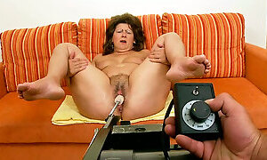 Fat cougar chick is testing a new sex machine with her legs spread wide open